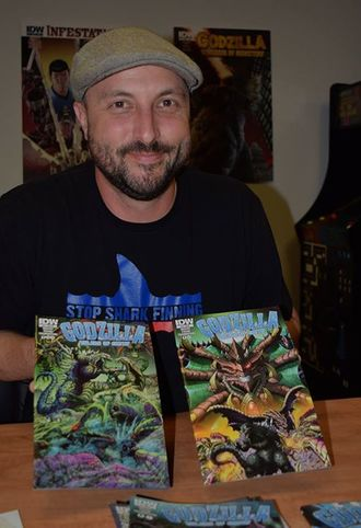 Chris Mowry with two issues of Godzilla: Rulers of Earth