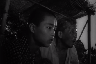 Kyohei (at left) and an islander warn of an incoming raft in Godzilla (1954)