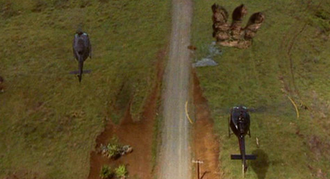 A UH-1 Iroquois flies over Godzilla's footprints in GODZILLA (1998)